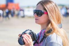 Onbekend meisje in zonnebril met een camera stock foto
