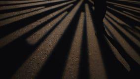 Onbekend, vrouw die in donkere straat lopen, die naar iets zoeken Lichten op grond stock footage