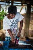 Onbekende jonge mens het afslachten vissen met een groot mes Het vuile Werk Harde arbeider Visser de vissen van de slagersholding stock foto