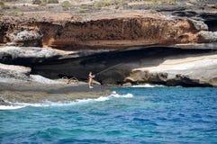 Onbekende mens die zich op het strand van oceaan en met de vissen van de hengelvangst bevinden Royalty-vrije Stock Afbeeldingen