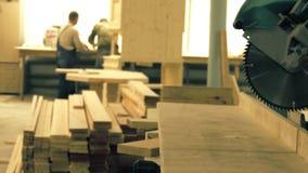 Onbekende timmerlieden en een figuurzaag in een timmerwerkworkshop stock video