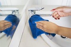 Onbekende vrouwenhanden die een tapkraan schoonmaken stock foto