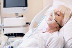 Onbewuste bejaarde dame die moeilijkheden ervaart terwijl ademhaling stock afbeelding