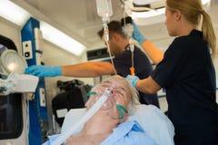 Onbewuste patiënt met zuurstofmasker in ziekenwagen Stock Foto