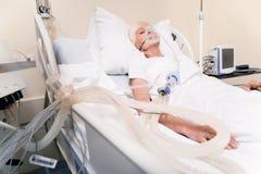 Onbewuste ziekelijke vrouw die noodzakelijke het levenssteun krijgt stock afbeelding