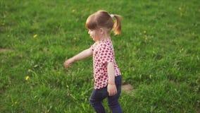 Onbezorgd meisje die op gras in park dansen stock footage