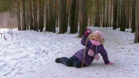 Onbezorgd meisje die op sneeuw in spel van het de winter het bos Grappige meisje in de winterbos liggen stock video