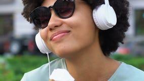 Onbezorgd mengen-rasmeisje die aan favoriet lied luisteren, die roomijs, geluk eten stock video
