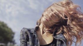 Onbezorgd model met krullend haar in het geruite overhemd die van het leven in langzame motie genieten stock videobeelden