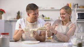Onbezorgd paar die onhandig deeg kneden, die pret in keuken, ongeschikte chef-koks hebben stock videobeelden