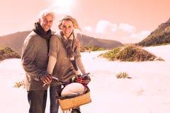 Onbezorgd paar die op een een fietsrit en picknick gaan op het strand Royalty-vrije Stock Afbeeldingen