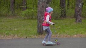Onbezorgd tienermeisje die een autoped berijden op weg in het groene park van de de lentestad stock footage
