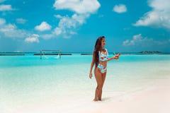 Onbezorgde bikinivrouw op tropisch strand Vrij slank meisje die met coctail op exotisch eiland in turkooise oceaan genieten van B royalty-vrije stock foto