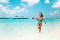Onbezorgde bikinivrouw op tropisch strand Vrij slank meisje die met coctail op exotisch eiland in turkooise oceaan genieten van B stock foto