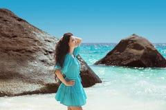 Onbezorgde donkerbruine vrouw die in blauwe kleding van het leven genieten dichtbij seashor Royalty-vrije Stock Afbeelding