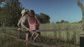 Onbezorgde familie die in platteland bij zonsondergang rusten stock videobeelden