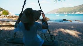 Onbezorgde gelukkige vrouw in hoed op schommeling bij mooi paradijsstrand in Thailand stock video