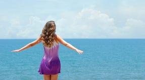 Onbezorgde gelukkige vrouw in kleding en vrije open wapens op kust bij zon royalty-vrije stock afbeeldingen