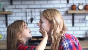 Onbezorgde jonge moeder en dochter die in de keuken voor de gek houden Het mamma en het kind hebben samen pret stock video