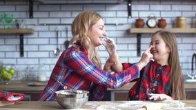 Onbezorgde jonge moeder en dochter die in keuken het koken bij de keukenlijst voor de gek houden Het mamma en het kind hebben sam stock footage