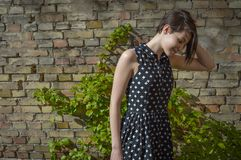 Onbezorgde jonge vrouw die zich voor oude bakstenen muur bevinden Stock Fotografie