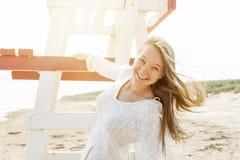 Onbezorgde jonge vrouw op strand Stock Afbeelding
