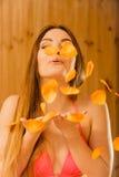 Onbezorgde jonge vrouwen blazende bloemblaadjes in sauna Stock Afbeeldingen