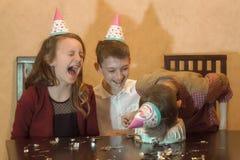 Onbezorgde kinderen bij een verjaardagspartij kid& x27; s gezicht in de verjaardagscake stock fotografie