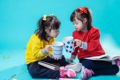 Onbezorgde kleine zusters met geestelijke wanorde die reuzekoppen clinking stock fotografie