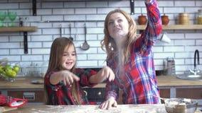 Onbezorgde leuke jonge moeder en dochter die in de keuken voor de gek houden Het mamma en het kind hebben samen pret stock video