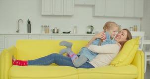 Onbezorgde mamma en dochter die pret op bank hebben stock video