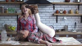 Onbezorgde mooie jonge die moeder en dochter in bloem zwaar wordt bevuild die in de keuken voor de gek houden Het mamma en het ki stock footage