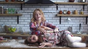 Onbezorgde mooie jonge die moeder en dochter in bloem zwaar wordt bevuild die in de keuken voor de gek houden Het mamma en het ki stock video
