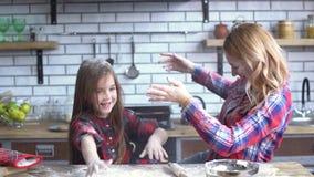 Onbezorgde mooie jonge moeder en dochter die in de keuken voor de gek houden Het mamma en het kind hebben samen pret stock footage
