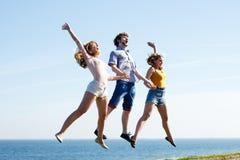 Onbezorgde vrienden die door overzeese oceaan springen Stock Foto