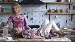 Onbezorgde vrij jonge die moeder en dochter in bloem zwaar wordt bevuild die in de keuken voor de gek houden Het mamma en het kin stock footage