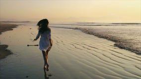 Onbezorgde vrouw in barefeet die naar overzees tijdens zonsondergang lopen stock videobeelden