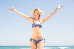 Onbezorgde vrouw in bikini die zich op het strand bevinden Stock Afbeeldingen
