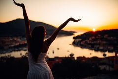 Onbezorgde vrouw die in aard, mooie rode zonsondergangzonneschijn genieten van Het vinden van binnenvrede Geestelijke helende lev stock fotografie