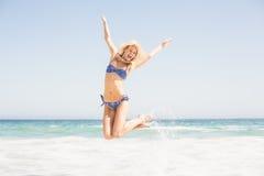 Onbezorgde vrouw die in bikini op het strand springen Stock Foto's