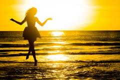 Onbezorgde vrouw die in de zonsondergang op het strand danst vakantie vitaliteit gezond het leven concept vakantievita Stock Afbeeldingen