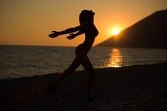 Onbezorgde vrouw die in de zonsondergang op het strand danst vakantie vitaliteit gezond het leven concept vakantievitaliteit gezo stock foto's