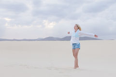Onbezorgde vrouw die van vrijheid op strand genieten Royalty-vrije Stock Afbeelding