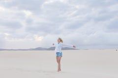 Onbezorgde vrouw die van vrijheid op strand genieten Royalty-vrije Stock Foto's