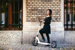 In onbezorgde vrouw op schopautoped in stedelijk landschap Royalty-vrije Stock Afbeelding