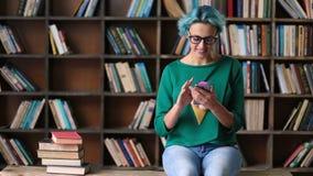 Onbezorgde vrouwelijke student die telefoon in bibliotheek met behulp van stock footage
