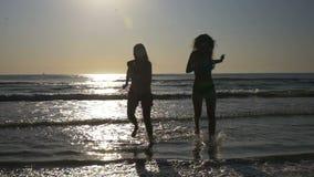 Onbezorgde vrouwen die op de kust dansen en naar een zandig strand in langzame motie lopen stock footage