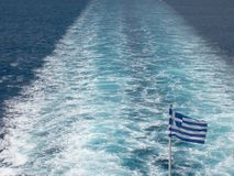 Onboard a ferry in the aegean sea. Flag of ferry's stern while somewhere in the aegean Royalty Free Stock Photo