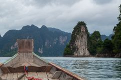 Onboard a longtail boat on Cheow Lan lake. Heading towards spectacular limestone formations that are rising out of the water Stock Photos