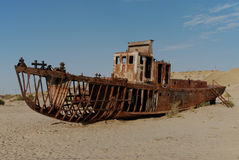 Once the Aral Sea, now a desert. Rusty ship lying in the sand at the former Soviet Aral Sea port of Moynaq in Uzbekistan Stock Images